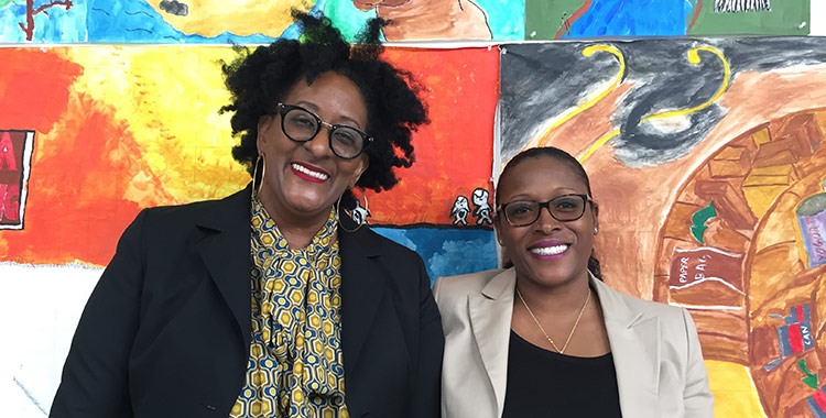 Professors Faith Armstrong and Tameka Battle in front of colorful paintings