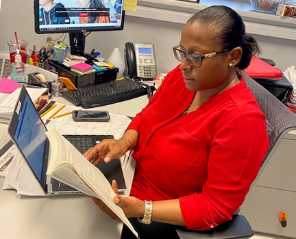 Professor reading and working at her desk
